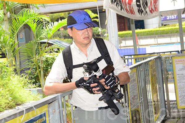 这名帮凶用大型摄影机对准学员拍摄。(摄影:邝天明/大纪元)
