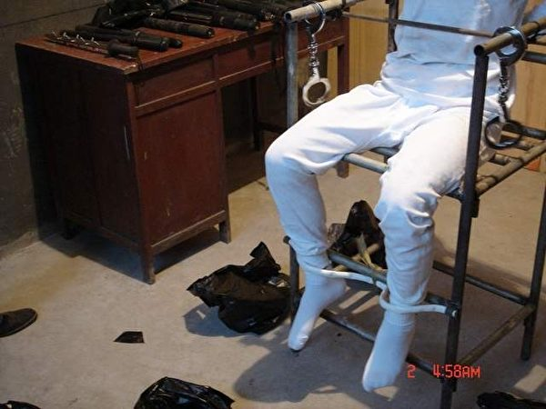 酷刑演示图:雷明被固定在铁老虎椅上双脚离地,一根铁棍横穿扶手内侧紧紧贴着小腹,双手反背铐。(明慧网)
