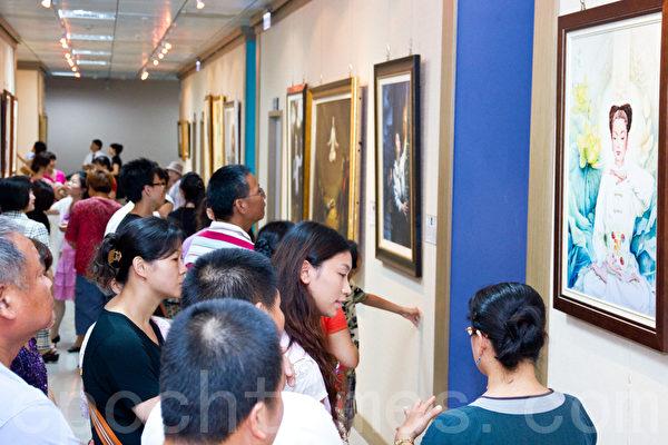 真善忍國際美術巡迴展覽7日在彰化市婦女學苑展出,導覽人員(右一)為民眾導覽。(攝影:陳柏州 / 大紀元)