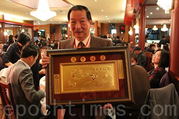 大洋洲台灣商會聯合總會吳天佐總會長展示世界台灣商會聯合總會贈與的金匾。(攝影:劉珍/大紀元)