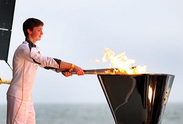 查尔斯‧罗杰斯传递火炬抵达终点站伯恩茅斯,并点燃奥运圣火。(图片来源:Getty Images)