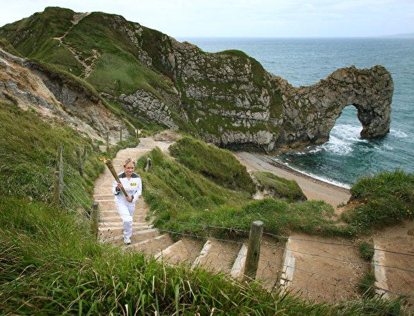 莉莎‧迪瓦恩(Lisa Devine)在侏罗纪海岸的著名景点多尔多门(Durdle Door)传递奥运圣火。(图片来源:Getty Images)