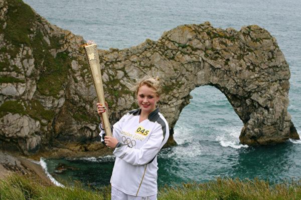 莉莎‧迪瓦恩(Lisa Devine)手举火炬在侏罗纪海岸的著名景点多尔多门(Durdle Door)。(图片来源:Getty Images)
