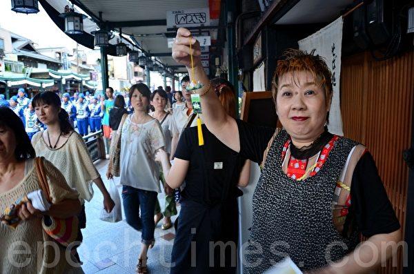 路边经营一家日本面的老板娘兴奋地随着天国乐团的节奏不断地打着拍节,还手拿小莲花高兴的合影。(摄影:刘洋/大纪元)
