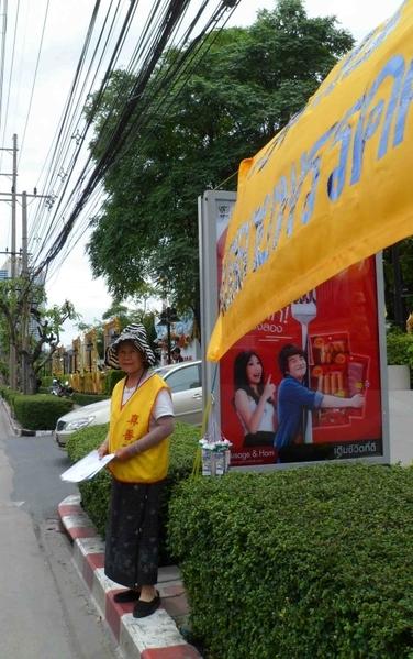 泰国曼谷中共大使馆前,一位72岁的泰籍华人老太太还是一如既往地每周五天准时在对面马路拉横幅抗议中共对中国法轮功学员的残酷迫害。在7月18日,还换上了一条更大更长的新横幅。(摄影:史丹云/大纪元)