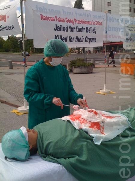 在國際器官移植會議開會地點前,法輪功學員演示中共活體摘除器官。(攝影:劉成/大紀元)