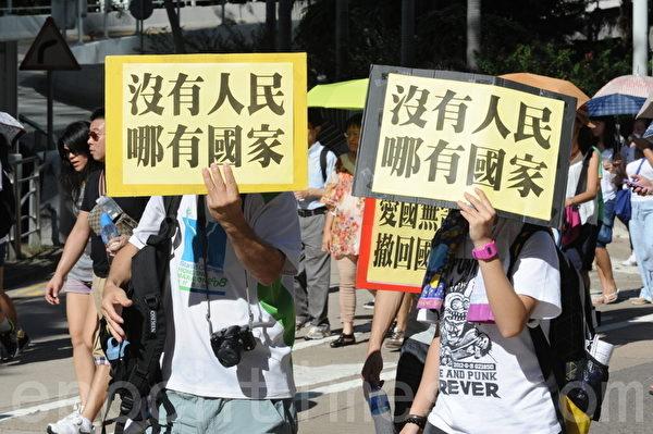 市民高舉自製抗議標語牌(攝影:孫青天/大紀元)