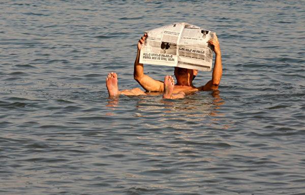 死海含盐量高,有惊人地浮力,让任何人轻易浮在水面。(GALI TIBBON / AFP)