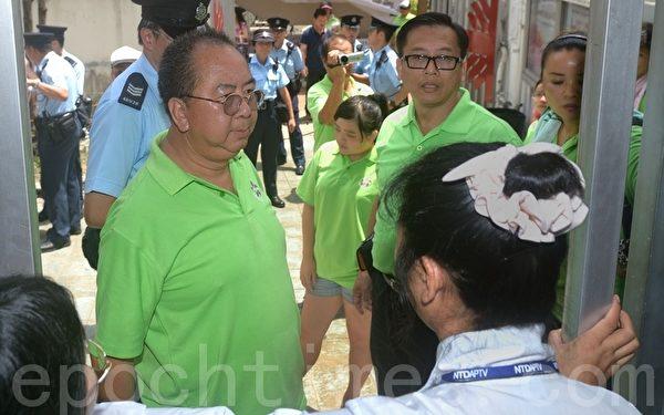 在頭目林國安(綠衣左一)發令下,幫兇一次又一次企圖衝入大門口,想進入比賽會場,被主辦方保安人員及明愛中心職員阻止。(攝影:宋祥龍/大紀元)
