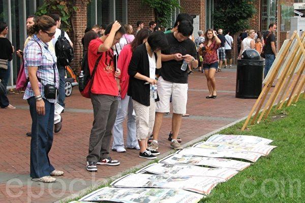 中、西游客在阅读中共迫害法轮功的真相资料(摄影:良克霖/大纪元)