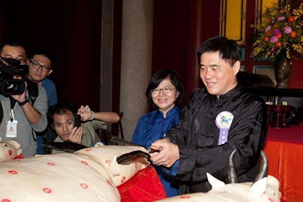 台北市政府28日在孔廟舉行「釋奠典禮」,市長郝龍斌(右)在典禮結束後,依照禮俗切智慧榚分送給現場參禮的民眾。(台北市政府提供)