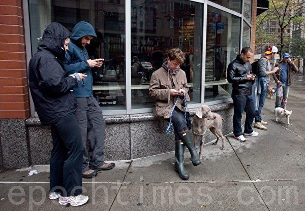人們倚靠在紐約市第六大道一家咖啡館的窗旁﹐利用免費的無線網絡連接(攝影﹕Amal Chen/大紀元)
