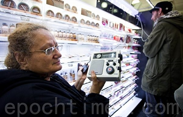 Alexa Cruz女士在曼哈頓中城一家Duane Reade店裡從收音機上接收桑迪颶風的最新情況。許多紐約人都跑到便利店和餐館去給他們的設備充電。(攝影﹕Amal Chen/大紀元)