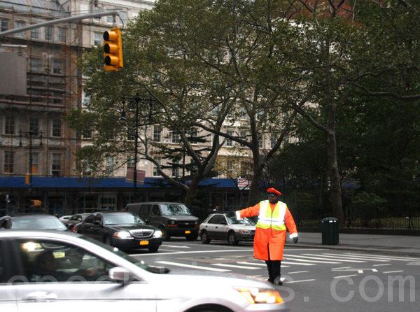 曼哈頓下城因斷電陷入黑暗﹐交通燈也不亮﹐由交警指揮交通﹐入夜交警使用熒光棒。(攝影﹕蔡溶/大紀元)