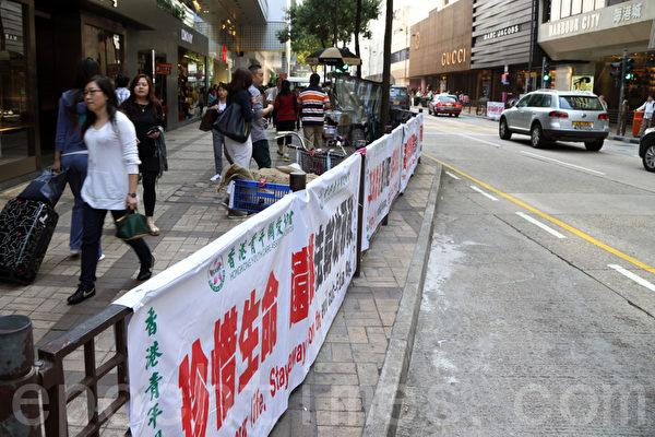 有中共勢力背景的惡黨團伙在廣東道馬路兩旁掛滿污衊攻擊法輪功的橫幅,正在受到許多正義市民的唾罵與抵制。(攝影:潘在殊/大紀元)