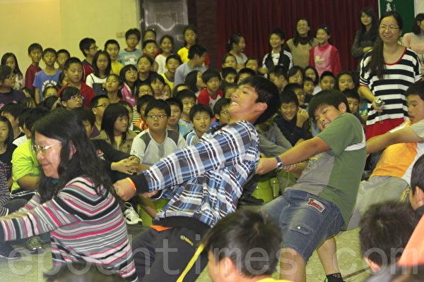 小朋友試著「挑戰大力士」(攝影:徐乃義/大紀元)