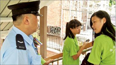 ↑關愛協會的年輕女惡徒(右)被警員指證襲警,更辱罵警員「吃屎」。她在事發後逃到明愛門外天橋,警員前往登記她的身份證。(攝影:余鋼/大紀元)