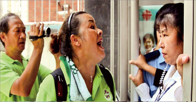 身穿綠色制服的「香港青年關愛協會」的暴徒圍攻舞蹈大賽會場,並多次衝擊明愛中心入口,試圖破壞大賽進行。(攝影:梁路思/大紀元)