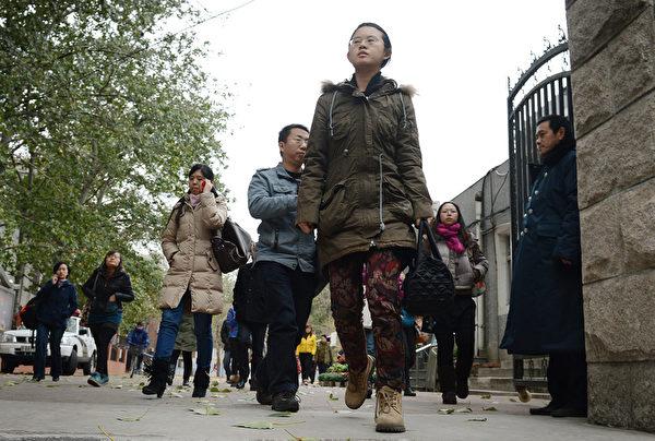 2013年中国国家公务员考试25日举行公共科目考试。本届国考计划招录2万多人,超150万人报名创新高。图为考生离开三里屯的一间学校。(AFP)