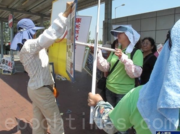 图为9月16日青关会团伙(绿衣)阻止法轮功学员(左一)以展板向大陆游客讲真相。(大纪元)