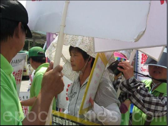 图为9月10日多名青关会团伙(绿衣)夹攻一名法轮功学员(右二),其中一人更手持扩音喇叭,滋扰学员外并阻止大陆游客听真相。(右一)(大纪元)