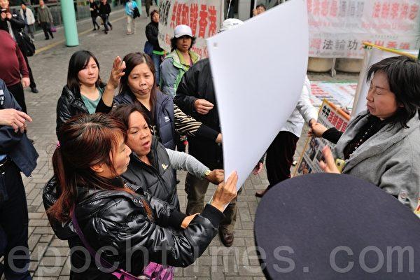 12月6日午后,青关会成员(左)一再冲击红磡法轮功真相点,法轮功学员(右)手拖着手守护真相点。(摄影:宋祥龙/大纪元)