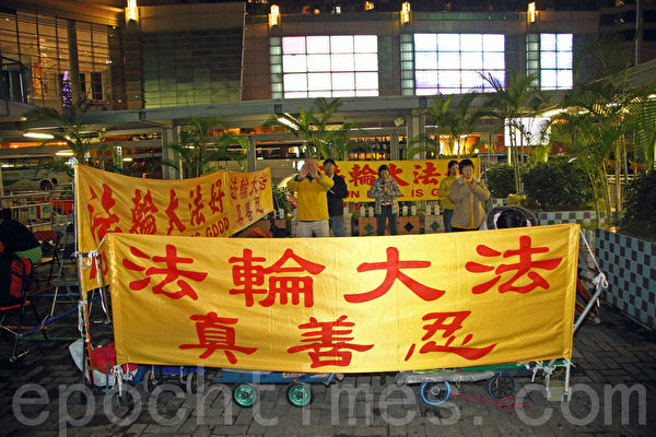 12月6日深夜,恶党团伙的横幅被清理后,法轮功学员在红磡真相点炼功。(摄影:潘在殊/大纪元)