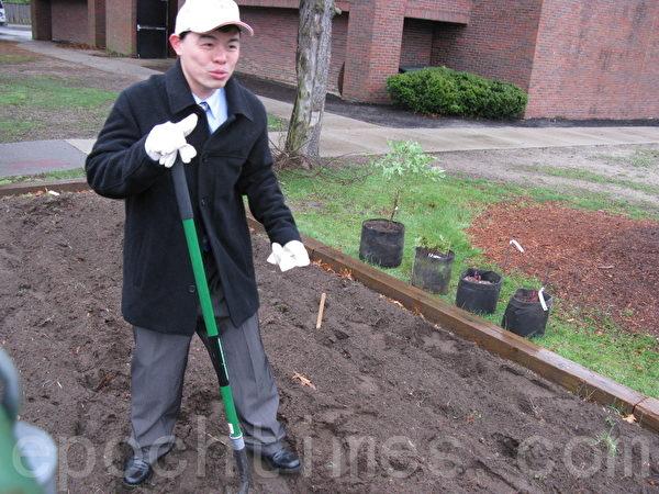 """黄正杰主任可说是""""志工中的志工""""﹐即便西装革履﹐也一样在泥泞的土中种花草。(摄影﹕冯文鸾/大纪元)"""