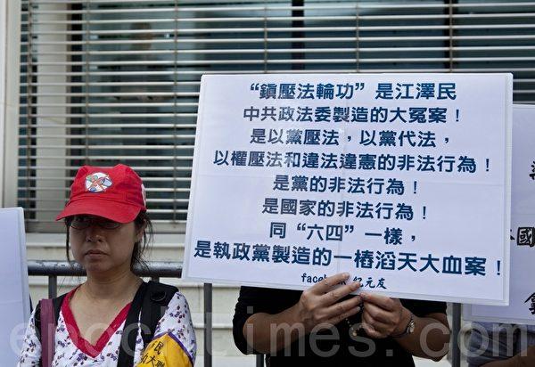遊行人士在中聯辦後門高舉抗議標語牌。(攝影:余鋼/大紀元)
