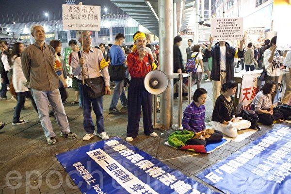 部份遊行人士還到位於銅鑼灣、紅磡火車站以及尖沙咀天星碼頭(圖)的法輪功真相點,聲援法輪功學員,並控訴青關會的惡行。(攝影:余鋼/大紀元)