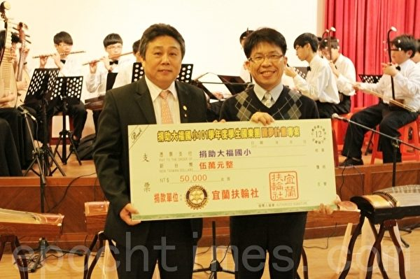 宜蘭扶輪社社長尤文忠(左)捐贈,由校長代表接受。(攝影:曾漢東/大紀元)