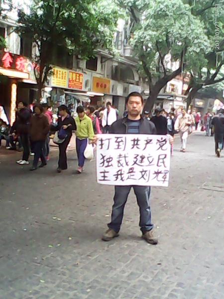 廣州「舉牌哥」劉輝在廣州繁華地段再次舉牌,實名舉出的標語是:「打倒共產黨獨裁!」和「共產黨是共匪!」。(知情者提供)