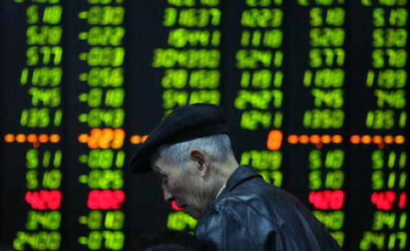 近日發佈的《中國股市形象報告(2012)》顯示,股民認為A股病入膏肓,自嘲「賺錢能力不如乞丐」。圖為一股民在電子報價牌前走過。(China Photos/Getty Images)