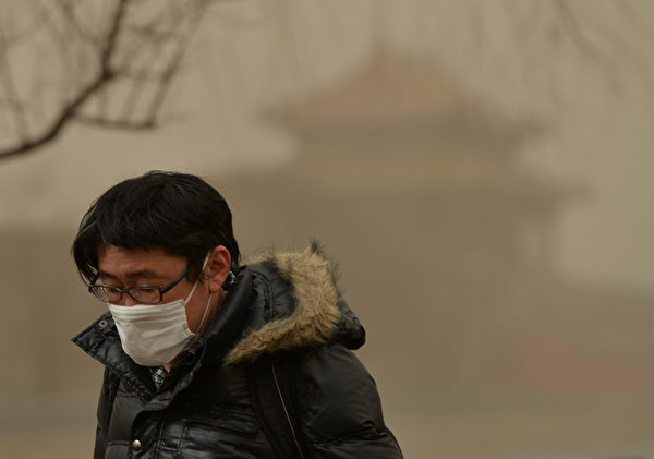 2013年2月28日,北京籠罩在霧霾與沙塵中,民眾紛紛戴上口罩掩護口鼻。(Mark RALSTON/AFP)