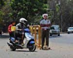 印度班加罗尔在路口设置纸板交警,希望吓阻司机违反交通规则,以期降低道路死亡人数。(Photo by Manjunath Kiran / AFP)