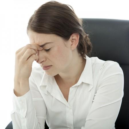 黑褐色头发的职业妇女因头痛手指捏着眉心