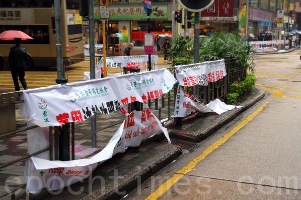 """中共镇压法轮功的元凶江泽民、曾庆红等在香港的恶行引起香港社会公愤,和香港市民的抵制,众多的香港市民要求香港政府取缔受中共操控的""""香港青年关爱协会""""在香港市面上的辱骂法轮功的横幅。图为""""香港青年关爱协会""""的非法横幅被不知名的市民清剿。(摄影:潘在殊/大纪元)"""
