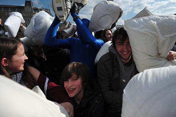 """当地时间2013年4月6日,英国伦敦的特拉法加广场,参与者用枕头互相击打对方,庆祝""""国际枕头大战日""""。(CARL COURT/AFP)"""
