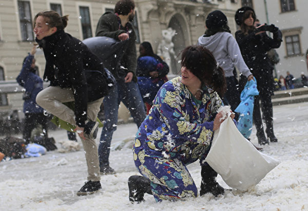 """当地时间2013年4月6日,奥地利维也纳玛丽亚·特雷西亚广场,参与者用枕头互相击打对方,庆祝""""国际枕头大战日""""。(ALEXANDER KLEIN/AFP)"""