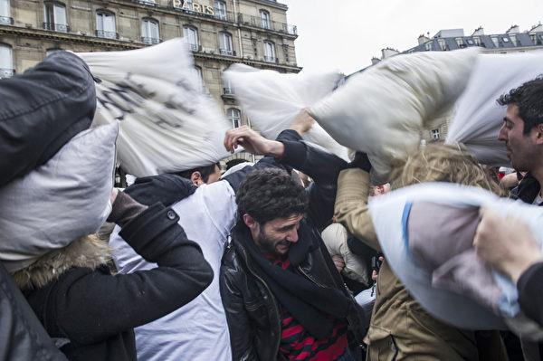 """当地时间2013年4月6日,法国巴黎的圣拉扎尔火车站前,参与者用枕头互相击打对方,庆祝""""国际枕头大战日""""。(FRED DUFOUR/AFP)"""