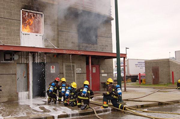 图:4月26日,温哥华消防队员靴子夏令营现场演习救火。图为培训基地的石头房屋室内着火,高中生消防队员正紧张灭火。(摄影:邱晨/大纪元)