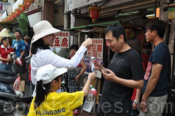 法轮功亲子学员将莲花及大法美好讯息,沿途分享给有缘的行人游客。(摄影:李晴玳/大纪元)
