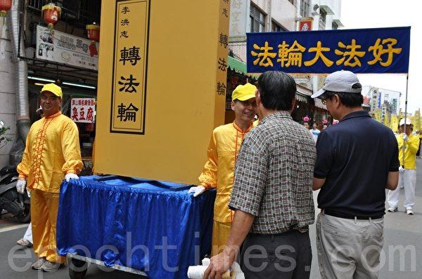 来自台北的游客陈先生(左)看到壮盛队伍,趋前向法轮功学员致意,并竖起大拇指连声称赞,法轮功很伟大!很了不起!(摄影:李晴玳/大纪元)