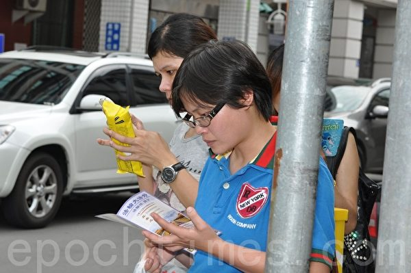 街旁民众拿到了法轮大法简介,迫不及待的专注阅读。(摄影:李晴玳/大纪元)