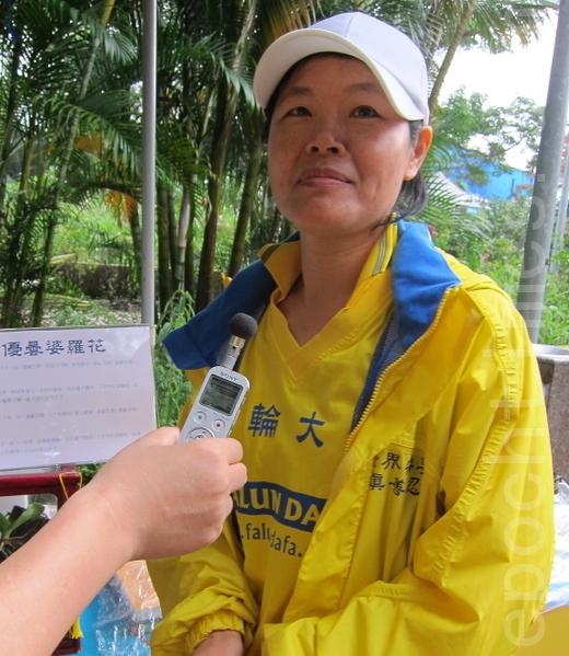 法輪功學員陳采楓表示,她很幸運得到法輪大法,她也很高興陸客看到「優曇婆羅花」,希望他們珍惜了解真相的機緣。(攝影:鍾元/大紀元)