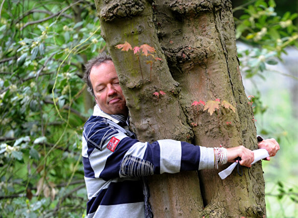 A man hugs a tree on May 14, 2013 at the Grugapark in Essen, western Germany. The WWF (World Wide Fund For Nature) environment protection organization and German tv channel ProSieben had called to pay special attention to trees during their