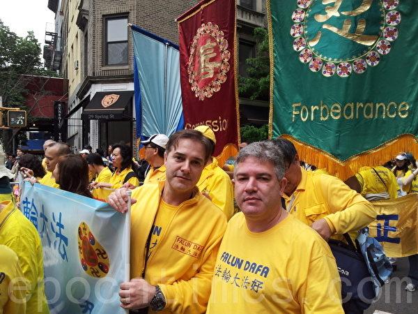 来自巴西的Danniel先生(右)被游行盛大场面感动得流泪。(摄影:陈天成/大纪元)