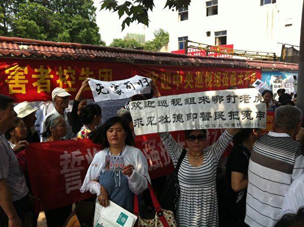 6月15日下午,湖北各地四百多冤民聚集在太平洋車站附近,舉著各種橫幅、標語喊冤。(訪民提供)