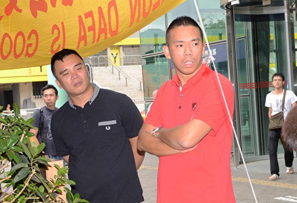 圖為疑凶(右)於2012年6月19日,干擾法輪功紅磡真相點。旁邊男子昨日也有出現在法庭。(大紀元資料圖片)