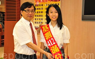 新興國際中小校長魏宏恩(左)為張荷莉同學祝賀。(攝影:徐乃義/大紀元)